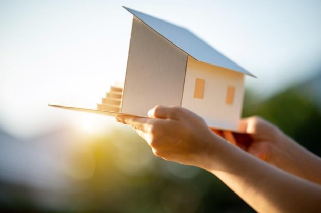 Handen met huismodelconcept geld besparen voor huis en onroerend goed.