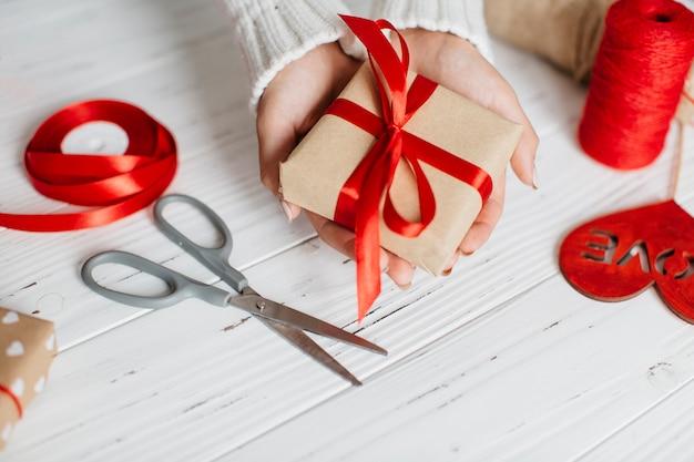 Handen met ingepakt cadeau voor valentijnsdag