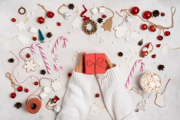 Handen met ingepakte geschenkdoos. kerstdecoratie met geschenkdozen, touw, marshmallows, peperkoekkoekjes