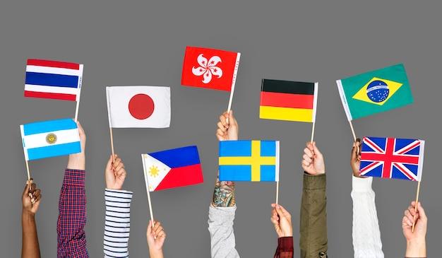 Handen met internationale vlaggen