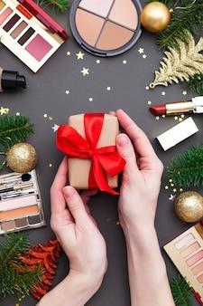 Handen met kerst geschenkdoos versierd rood lint.