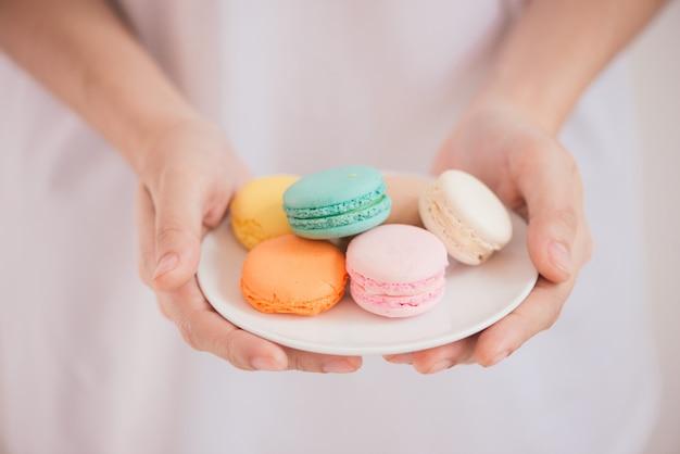 Handen met kleurrijke pastel cake macarons