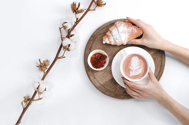 Handen met koffie en croissant en katoenen tak