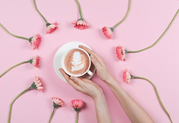 Handen met koffiekopje met bloemen
