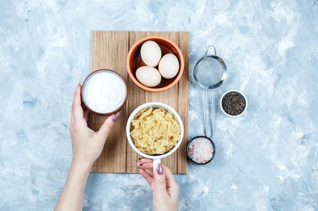 Handen met kommen yoghurt en pasta met eieren, zeef, kruiden plat lag op grungy grijs en snijplank achtergrond