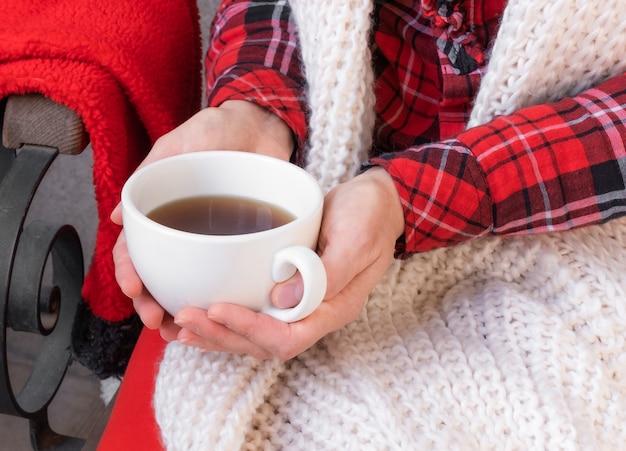 Handen met kopje thee of koffie gekleed in rode en witte kleren