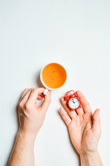Handen met kopje zwarte thee en rode wekker op witte ondergrond