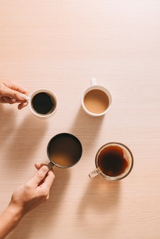Handen met kopjes koffie op houten oppervlak