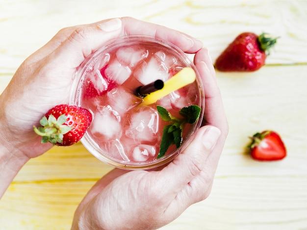 Handen met koude kopje aardbeien drinken