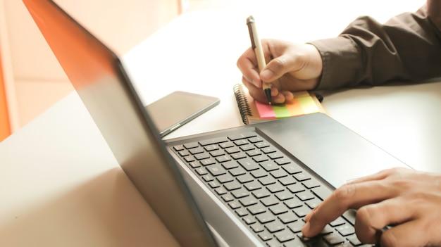 Handen met laptop en smartphone