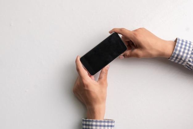 Handen met lege lege zwarte smartphone op een wit oppervlak, mockup-kopieerruimtes