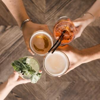 Handen met levendige drankjes roosteren