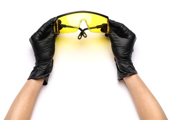 Handen met medische latexhandschoenen die beschermende bril houden
