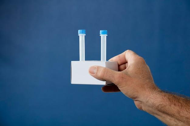 Handen met medium transportbuis kit voor pcr-analyse in kartonnen houder blauwe achtergrond