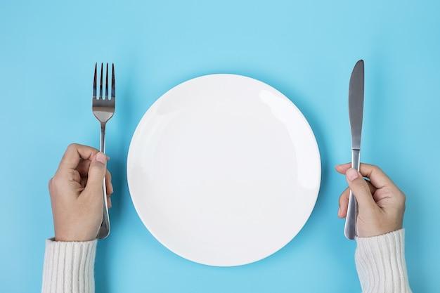 Handen met mes en vork boven witte plaat op blauwe achtergrond, dieet, gewichtsverlies, dineren en keukengerei concept