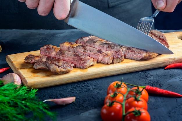 Handen met mes en vork een gekookte biefstuk snijden