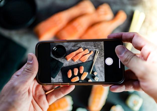 Handen met mobiel fotograferen van aziatische voedselsushi