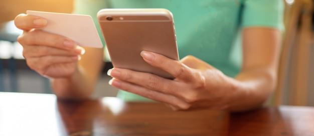 Handen met mobiele telefoon en creditcards