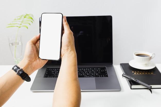 Handen met mobiele telefoon met laptopcomputer op tafel.