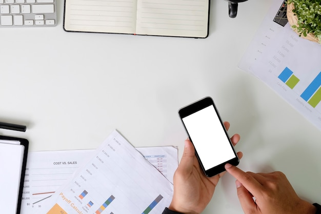 Handen met mockup-smartphone op de zakelijke tafel.