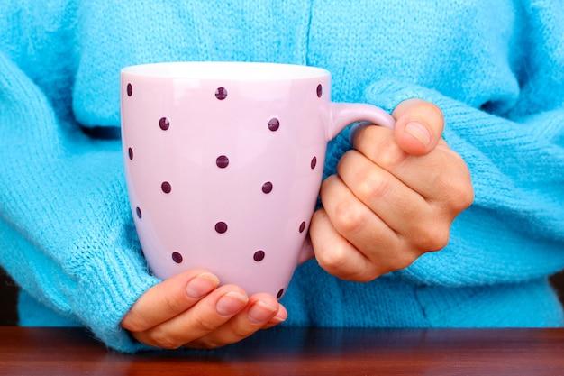 Handen met mok warme drank close-up
