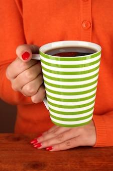 Handen met mok warme drank, close-up