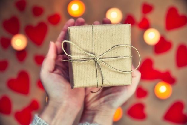 Handen met mooie geschenkdoos, vrouw cadeau geven, valentijnsdag, vakantie en begroeting seizoen concept, bovenaanzicht romantisch ontwerp als achtergrond