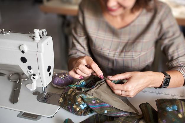 Handen met naald die kledingstukdetails aan elkaar naaien voordat u gaat naaien