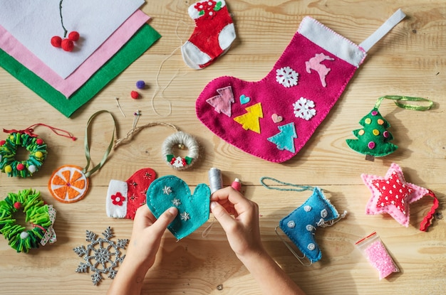Handen met naald en naaien vilten hart voor kerst- en nieuwjaarsdecor
