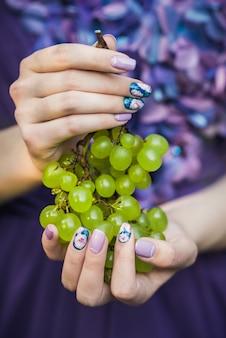 Handen met nagels druiven houden