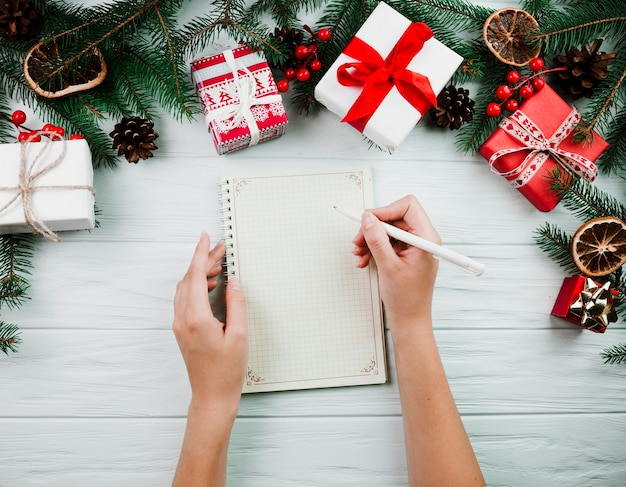 Handen met notitieboekje dichtbij kerstmistakje