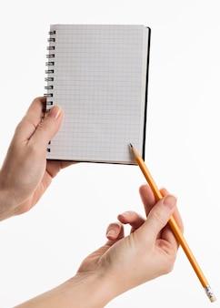 Handen met notitieboekje met potlood