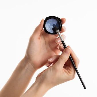 Handen met oogschaduw en make-up borstel