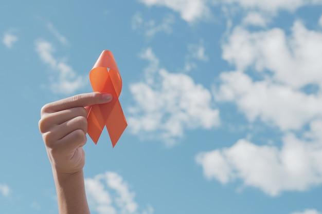 Handen met oranje lint over blauwe hemel