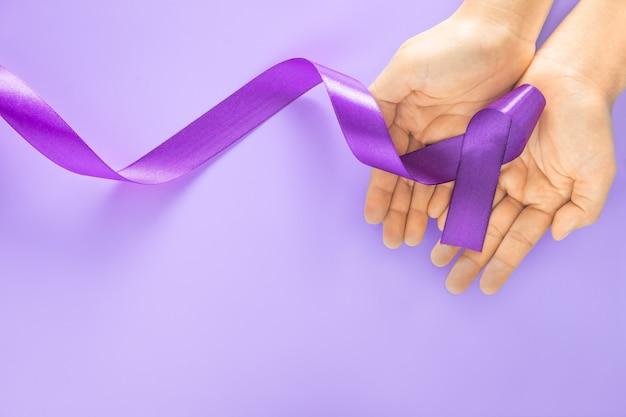 Handen met paars of violet lint op paarse ondergrond met kopie ruimte