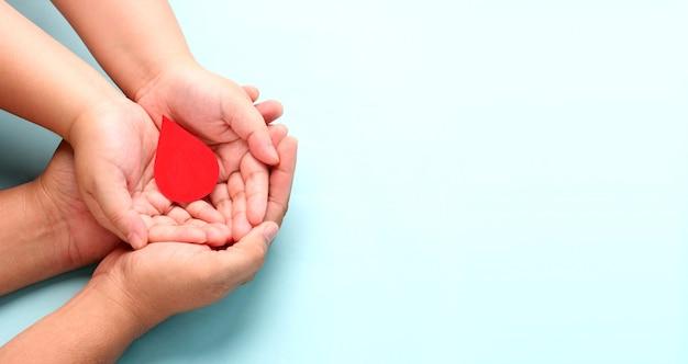 Handen met papier bloeddruppel op blauwe achtergrond.