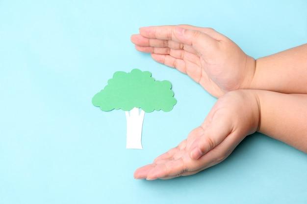 Handen met papier boom op blauw.