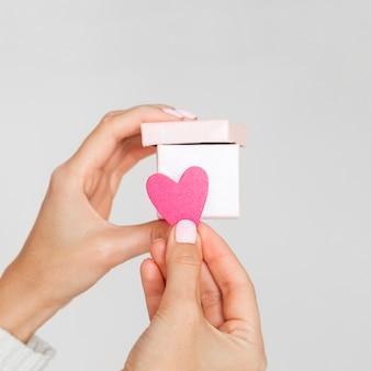 Handen met papier hart en doos