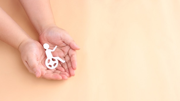Handen met papier uitgesneden persoon zit in rolstoel