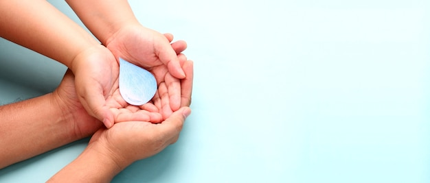 Handen met papier waterdruppel op blauwe achtergrond.
