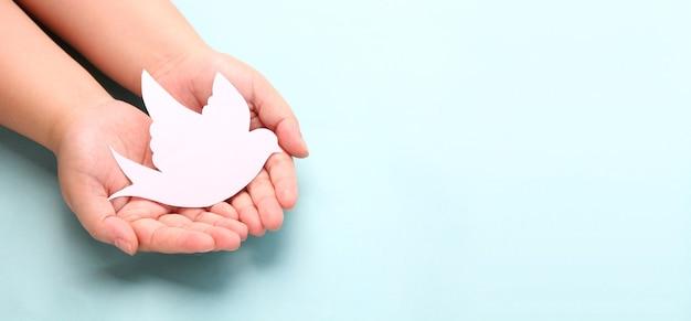 Handen met papier witte vogel, wereldvrede dag concept.