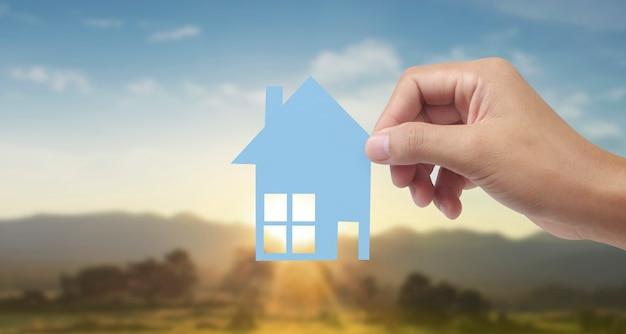 Handen met papieren huis, gezinswoning en bescherming van verzekeringsconcept