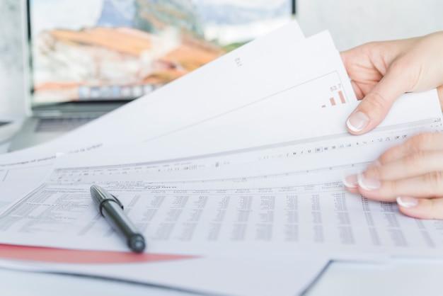 Handen met papieren met gegevens op bureau