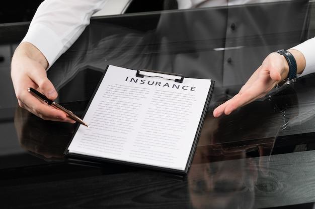 Handen met pen en verzekeringstabel