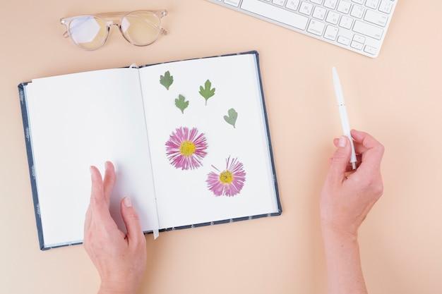 Handen met pen in de buurt van laptop met droge bloemen, toetsenbord en bril