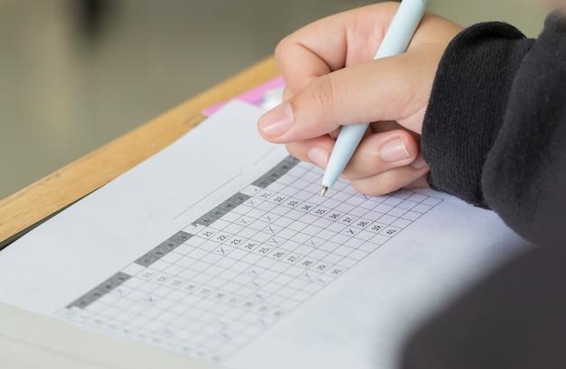 Handen met pen over aanvraagformulier, studenten die examens schrijven examen afleggen