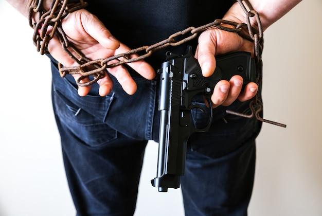 Handen met pistool in oude roestige kettingen. rover gearresteerd voor illegale misdaad. overvaller heeft de wet overtreden.
