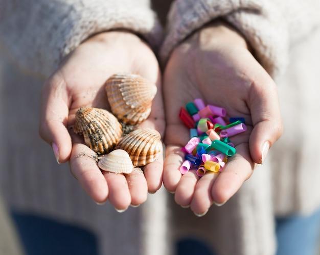 Handen met plastic en schelpen