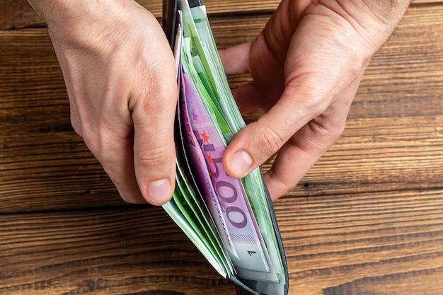 Handen met portemonnee vol geld bankbiljetten op houten tafel