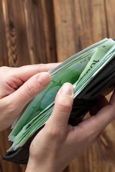 Handen met portemonnee vol geld bankbiljetten op houten